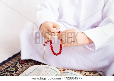 Ramadan Portrait - Hand of muslim kid making zikr using rosary (praying to Allah)