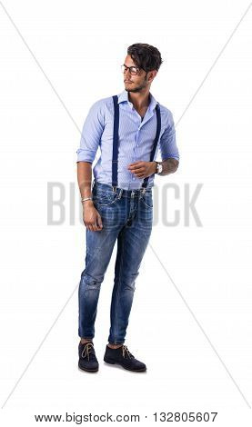 Portrait of brunette young man in light blue shirt, suspenders and jeans, standing in studio shot isolated against white background. Full length photo