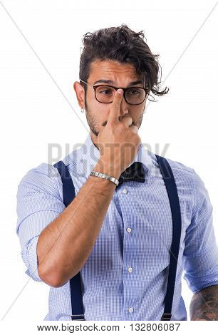 Portrait of brunette young man in glasses, bow-tie, suspenders and shirt looking away. Studio shot