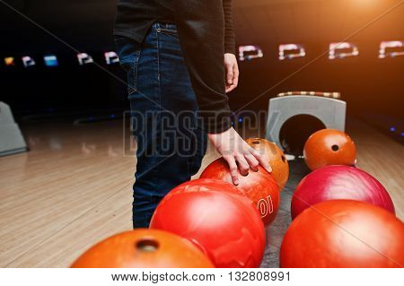 Close Up Of Bowling Player Hand Taking Red Ball From Bowl Lift