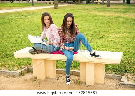 two girls were photographed on a shop with the mobile phone and the book
