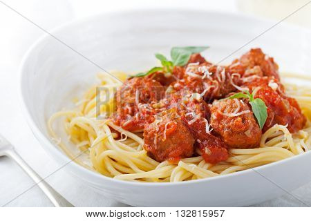 Meatballs in tomato sauce and fresh basil with spaghetti on a white background