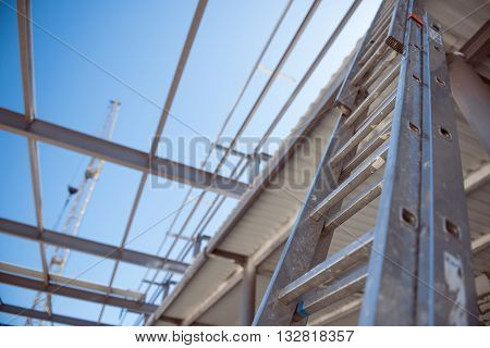 Stairs. Construction works of new industrial buildings with channel girders with crane and machines in a background