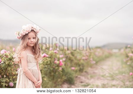 Smiling kid girl 4-5 year old posing in rose garden wearing stylish dress and flower hairband outdoors. Looking at camera. Childhood.
