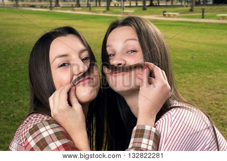 two beautiful girls in park play with hair