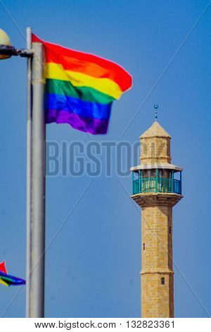 The minaret of Hassan Bek Mosque and a pride flag in the day of the Pride Parade in Tel-Aviv Israel poster