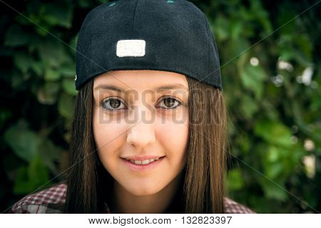 the stylish beautiful girl in a cap was photographed in park on walk