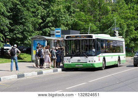 MOSCOW, RUSSIA - JUNE 4, 2016: Green public bus LIAZ on the bus stop on the Moscow city street. People on the bus stop are going to enter into the bus on summer day.