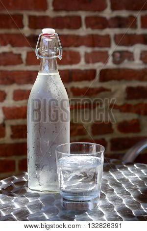 Bottle of cold water in hot summer day on brick wall background