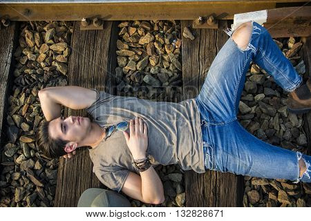 Attractive young man lying on railroad, wearing grey t-shirt and jeans, looking to a side