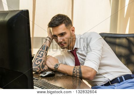 Tired bored young businessman sitting at his desk in front of his computer yawning, holding his head with his hand and eyes closed, in his office