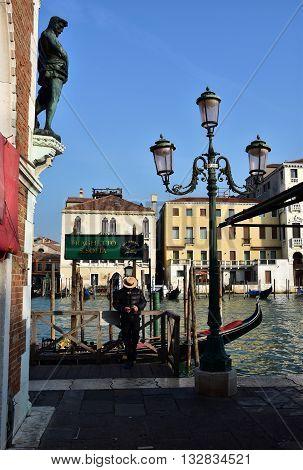 VENICE, ITALY - NOVEMBER 30: Venetian gondolier waiting for tourists besides Rialto Fish Market in the center of Venice NOVEMBER 30, 2015 in Venice, Italy