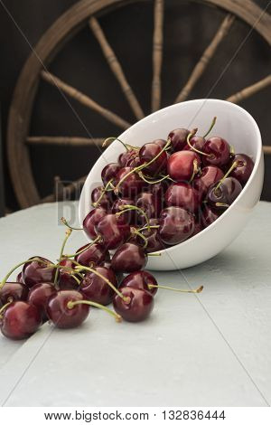 Cherries in a white bowl, stand on a blue wooden table with juice in a clay cup, with wooden wheel in beckground