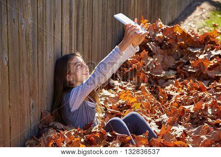 Tween kid girl selfie tablet pc in autumn leaves park