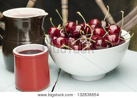 Cherries in a white bowl, stand on a blue wooden table with juice in a clay jug and cup, with wooden wheel in beckground