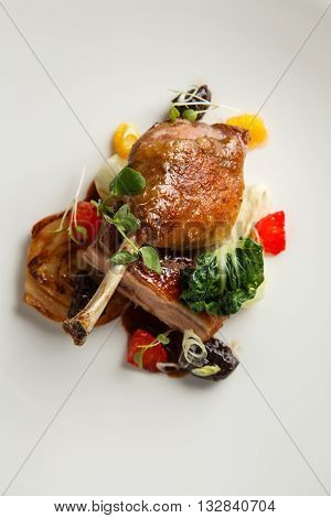 Well-browned and crisp duck confit with roast fennel, citrus fruit and prune sauce. Roasted duck leg. White dish.