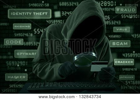 Internet Theft - a man wearing a balaclava looking at credit card code using magnifying glass