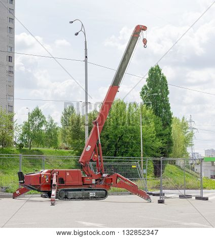 Red self propelled crane mounted on crawlers carrier with telescoping boom on an asphalt site against the backdrop of trees the sky and the urban