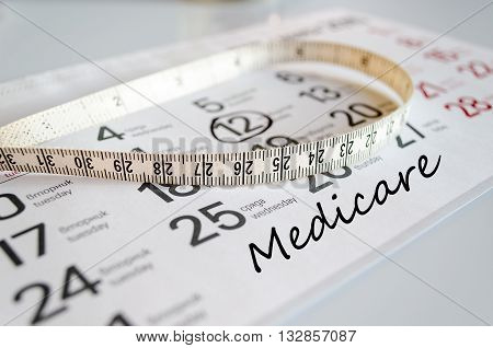 Medicare text concept over tape measure and calendar background