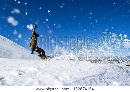Snowboader falling whilst racing through a Snowboard Cross Course - racing against the clock in the Australian Alps.