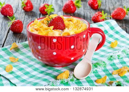 corn flakes with milk and strawberries in a red cup with wooden spoon on a table napkin on an old rustic table studio lights close-up top view