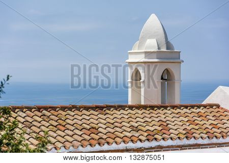 Church Bell tower against a blue mediterranean sea in Bb