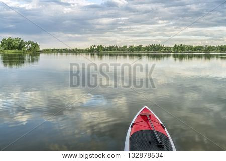 red stand up paddleboard with a paddle on calm lake - Arapaho Bend Natural Area, Fort Collins, Colorado