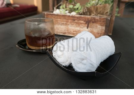 white scented rolled wet towel and cold drink to welcome a guest to thai aroma massage resort spa, Thailand.