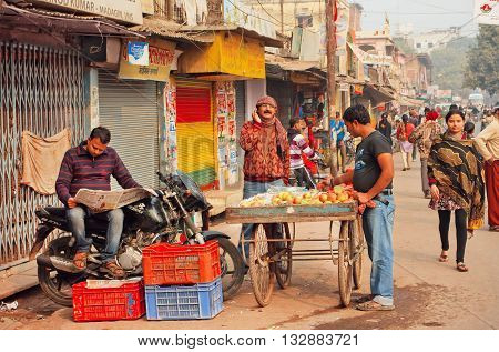 VARANASI, INDIA - JANUARY 2, 2016: Morning of indian city with farm traders and man reading newspaper on January 2, 2016. Varanasi urban agglomeration had a population of 1,435,113