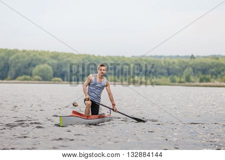 Chelyabinsk Russia - May 28 2016: athlete canoeist with an oar in a canoe after finish during Ural championship in rowing