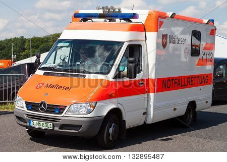 BERLIN / GERMANY - JUNE 3 2016: german ambulance car from Malteser drives on a street in Berlin / Germany on may 3 2016.