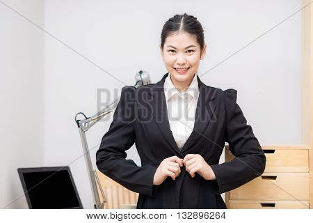 Smiling Asian Businesswoman With Laptop Computer Posting In White Office