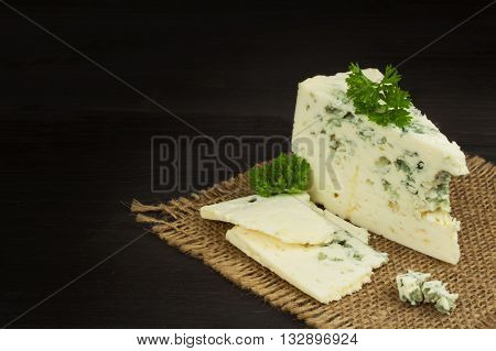 Danish blue. Blue cheese close up on an old wooden table. Preparing food blue cheese. Cheese on the kitchen table. Noble rot. Cheese with mold delicacy.