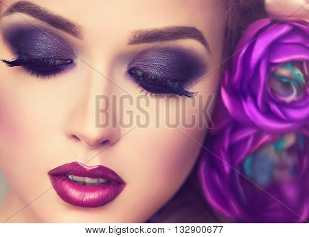 Summer  girl. Beautiful model with flower wreath on her head . Purple Makeup smoky eyes . Spring  girl with trendy make up . Hairstyle curly ponytail with violet   artificial rose flowers in  hair .