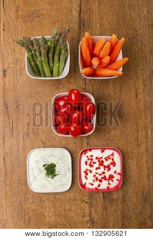 Top view of party food, asparagus, carrots, cherry tomatoes and yogurt dip with pomegranate seeds