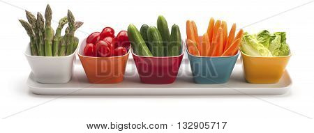 Asparagus, cherry tomatoes, cucumbers, carrots and lettuce hearts in small colorful bowls