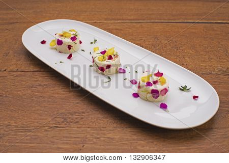 Three bite-size mini cheesecakes on a white porcelain plate decorated with colorful flower petals. Gourmet food.