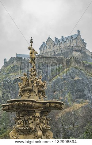The golden Ross fountain in Princess street gardens in Edinburgh Scotland creates a beautiful setting with the historic castle in the background.