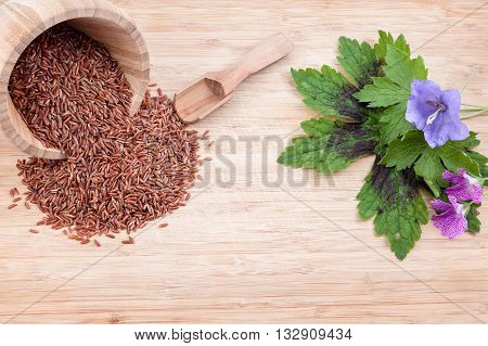 these herbs are red Camargue rice in an wooden bowl with spoon