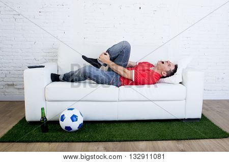 fanatic football fan lying on couch sofa with ball on green grass carpet emulating soccer stadium pitch mocking player in pain hurt on ankle in crazy supporter parody concept poster