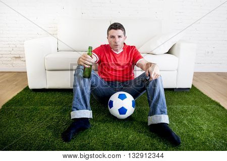 football fan cheering watching focused television soccer match suffering stress nervous wearing red team jersey sitting off couch on grass carpet with ball emulating stadium pitch