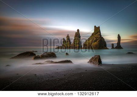 Black beach Reynisfjara and Reynisdrangar rocks at sunrise Iceland