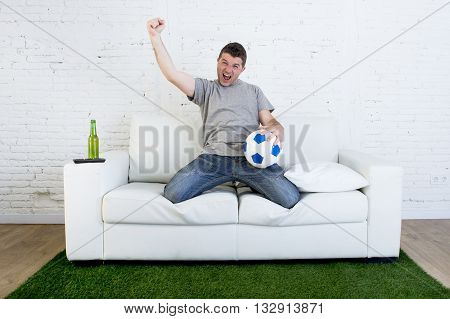 crazy football fan cheering happy watching television soccer match celebrating scoring goal excited and euphoric holding ball on sofa couch on grass carpet emulating stadium pitch