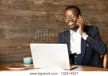 Business And Success Concept. Young African Financier, Working On Laptop, Making A Good Bargain On M
