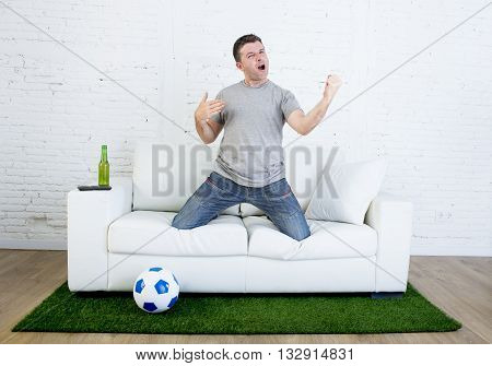 football fan cheering happy watching television soccer match celebrating scoring goal gesturing excited and crazy euphoric on sofa couch with ball on grass carpet emulating stadium pitch