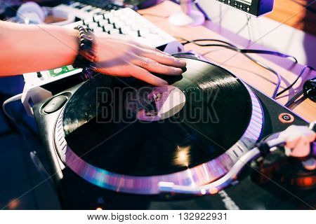 DJ creates composition in the recording studio.  DJ playing music in the recording studio. Studio record of new music track.