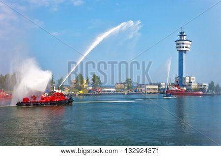 Fire fighting boat sprays water in port.