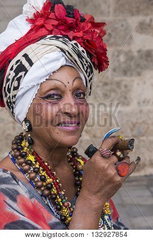 Havana, Cuba - january 19, 2016: Mature woman with typical attire, smoking a cigar in Havana, Cuba