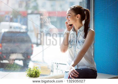 Keeping in touch. Cheerful and smiling young woman calling her best friend while sitting on a window sill and looking out of the window