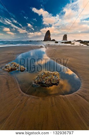 Quiet summer sunset at Cannon Beach, Oregon, USA - wet sand, clouds reflections in the water.